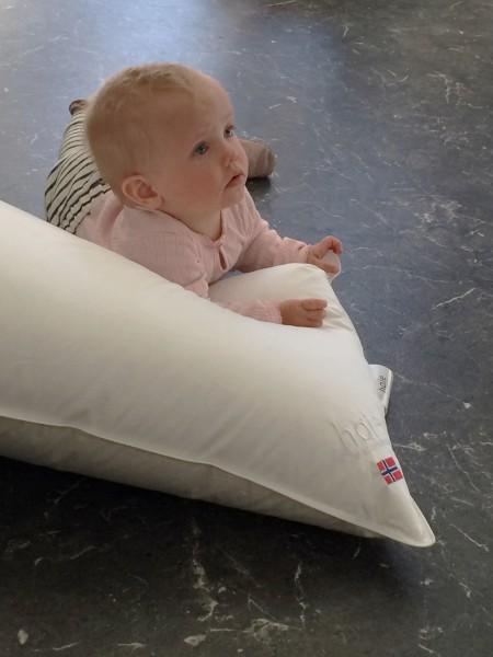 Liten jente på en stor Høie pute med gåsedun, foto Henning Høholt.
