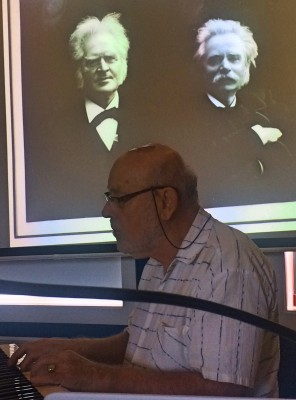 Torkil Bade presenterer boken ledsaket av bl.a. musikk  av Edvard Grieg, her fotografert sammen med Henrik Iv´bsen og Edvard Grieg på en presentasjon av boken i Drøbak Bibliotek.